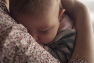 Routine versus Schedule: baby sleeping in mother's arms.