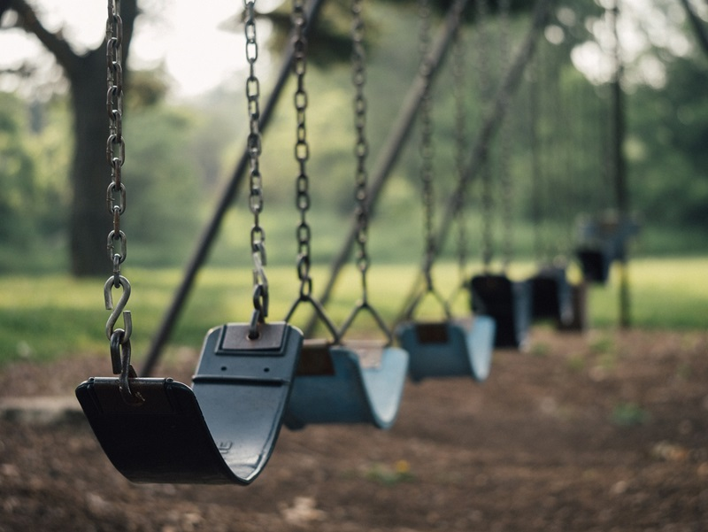 How to Get Your Child to Leave the Park: swings lining up neatly in a park