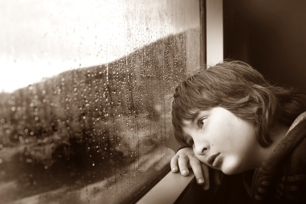 Emotions and Problem Solving: young boy staring out of a rain drenched window.