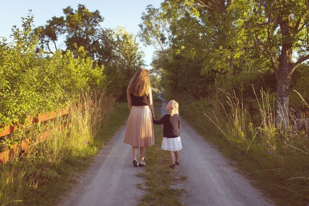 Emotions and Problem Solving: young mother holding little girl's hand, walking down the path.